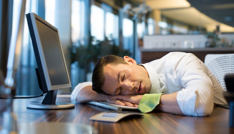 Shot of an office worker sleeping on his table - tired with working on citations and his NAP for SEO performance