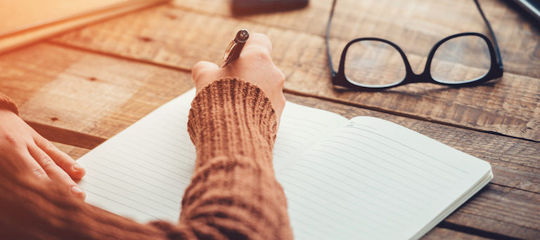 Close-up image of woman writing in notebook with copy space while sitting at the rough wooden table